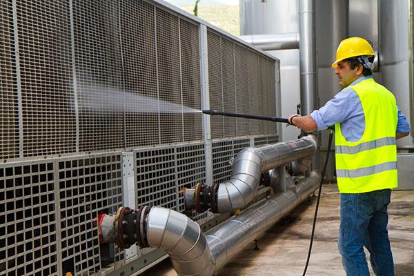 pracownik GB Clean podzczas czyszczenia maszyny przemysłowej